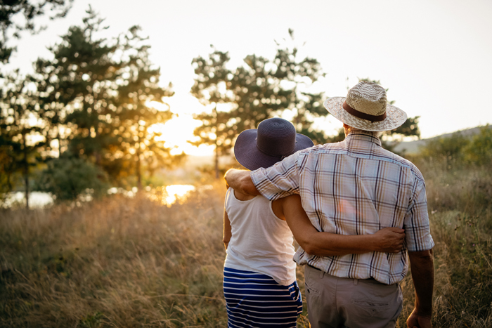 couple standing in field watching the sun set
