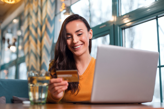 woman sitting at table with laptop looking at credit card