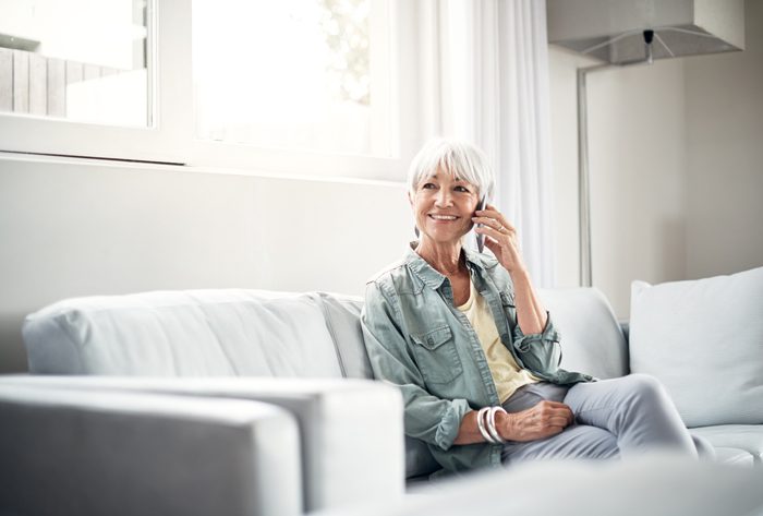 woman talking on phone while sitting on couch